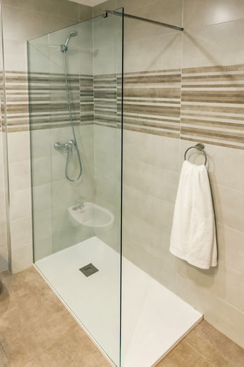 Reflection of glass of bathroom on tiled floor