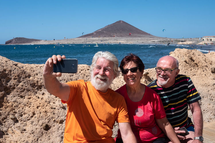 Friends taking selfie with smart phone while sitting against sea