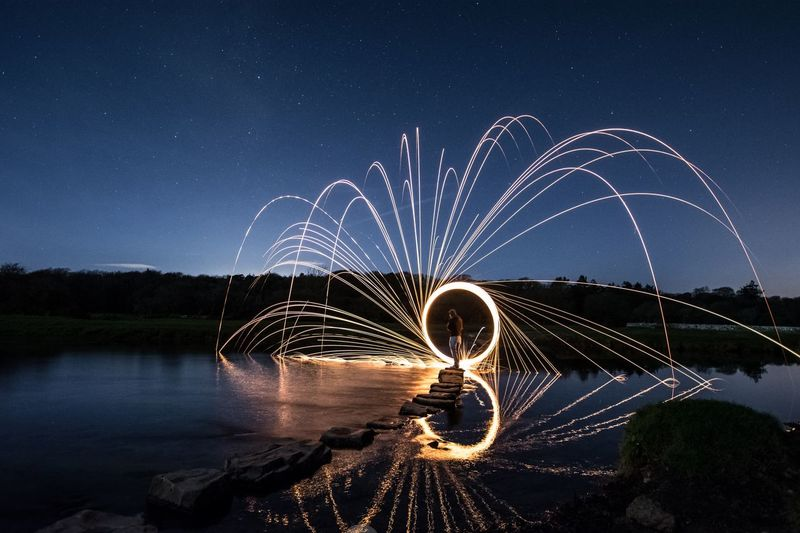 Man standing by wire wool at lakeshore against sky