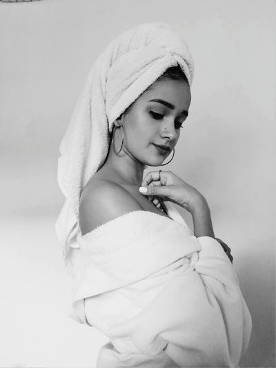Young Woman With Wrapped In Towel Standing Against White Background