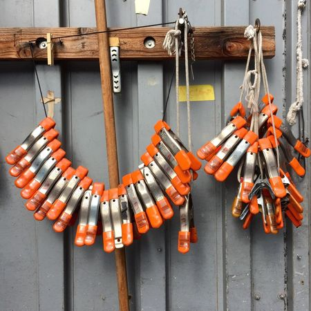 EyeEm Selects A set of Clamps Hanging Orange Color Safety No People Day Outdoors Close-up Metal Metallic Tools Work Grip Gadget Clamps Side By Side Repetition Wood Focus On Foreground