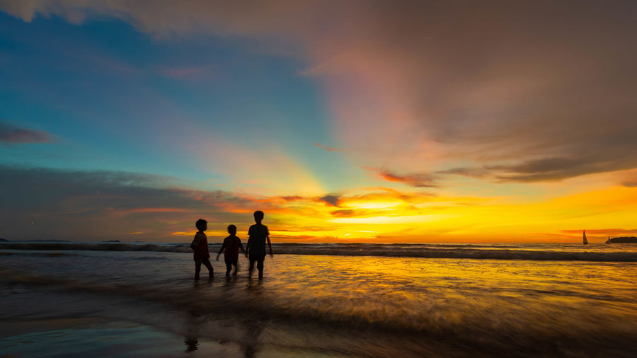 Sunset Sky Water Cloud - Sky Sea Beauty In Nature Scenics - Nature Beach Orange Color Land Real People Leisure Activity Silhouette Tranquility Togetherness Nature Tranquil Scene Horizon Over Water Lifestyles Outdoors Couple - Relationship