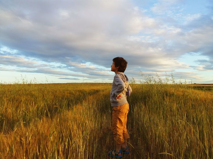Side View Full Length Of Boy Standing On Grassy Field Against Cloudy Sky