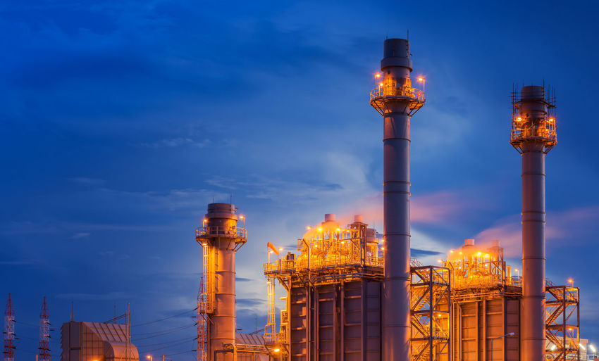 Low angle view of illuminated factory against sky at dusk