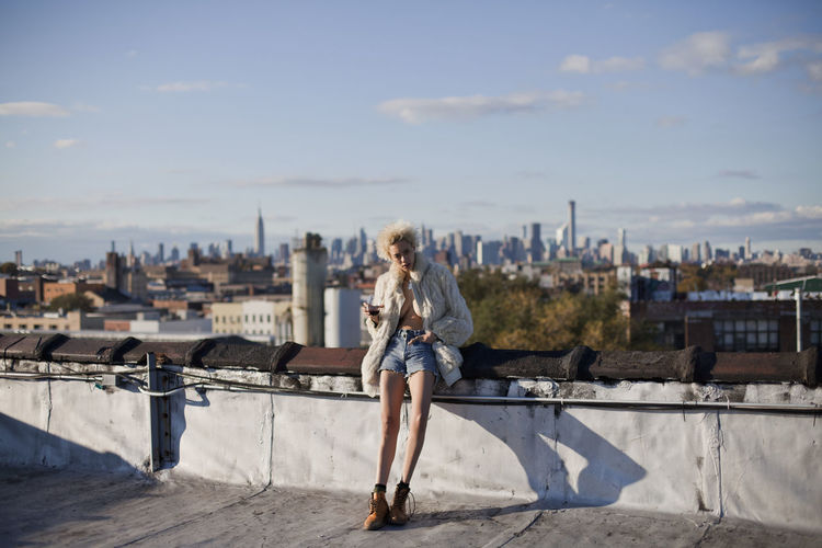 Full length of woman with cityscape against sky