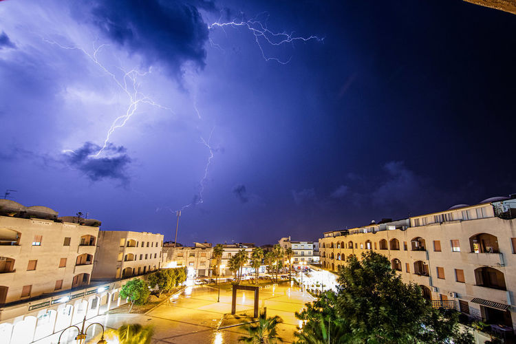 Panoramic view of lightning over buildings in city