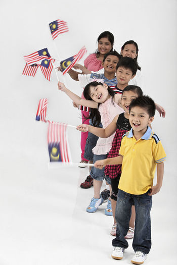 Cute friends waving malaysia flags while standing against white background