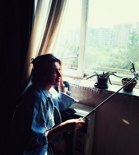 Woman taking selfie by window at home