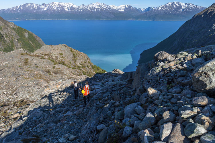 Beauty In Nature Blue Climbing Distant Fjord Full Length High Angle View Hiking Lyngen Alps Mixing Water Mountain Mountain Peak Mountain Range Nature Northern Norway Norway Outdoors Remote Rock - Object Rock Formation Rocky Mountains Snowcapped Mountain Stone - Object Tranquility Water