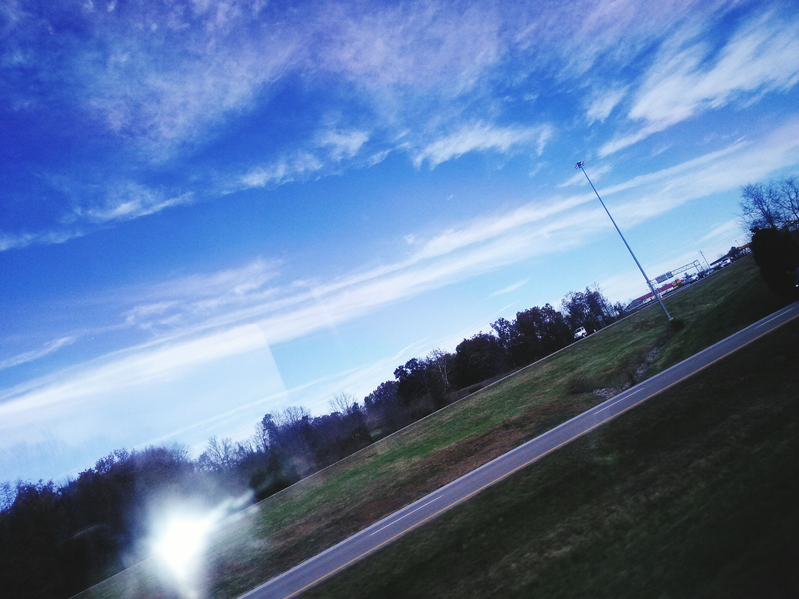 sky, cloud - sky, sunlight, sunbeam, blue, sun, nature, cloud, tree, beauty in nature, tranquility, low angle view, lens flare, silhouette, scenics, tranquil scene, outdoors, no people, landscape, day