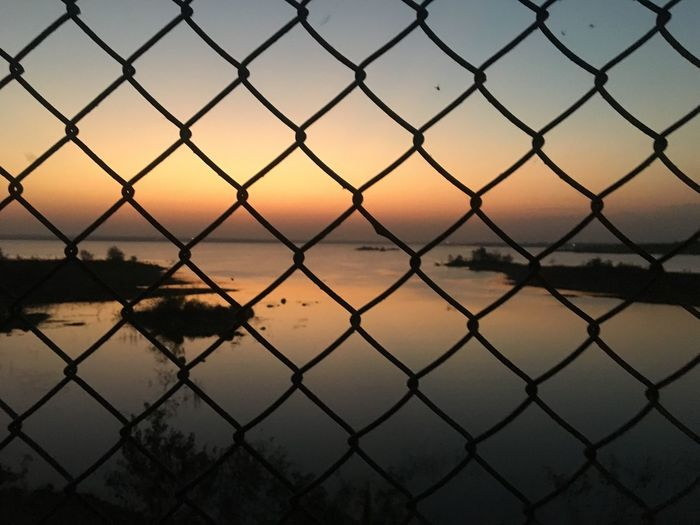 sunset 🌅 Chainlink Fence Sunset Sky Nature No People Water Tranquility Scenics Beauty In Nature Outdoors Silhouette