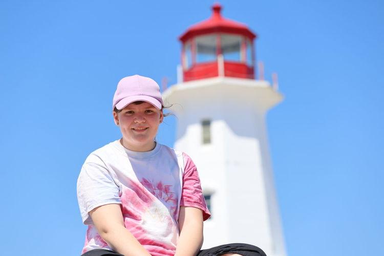 Portrait of smiling teenage girl sitting against lighthouse