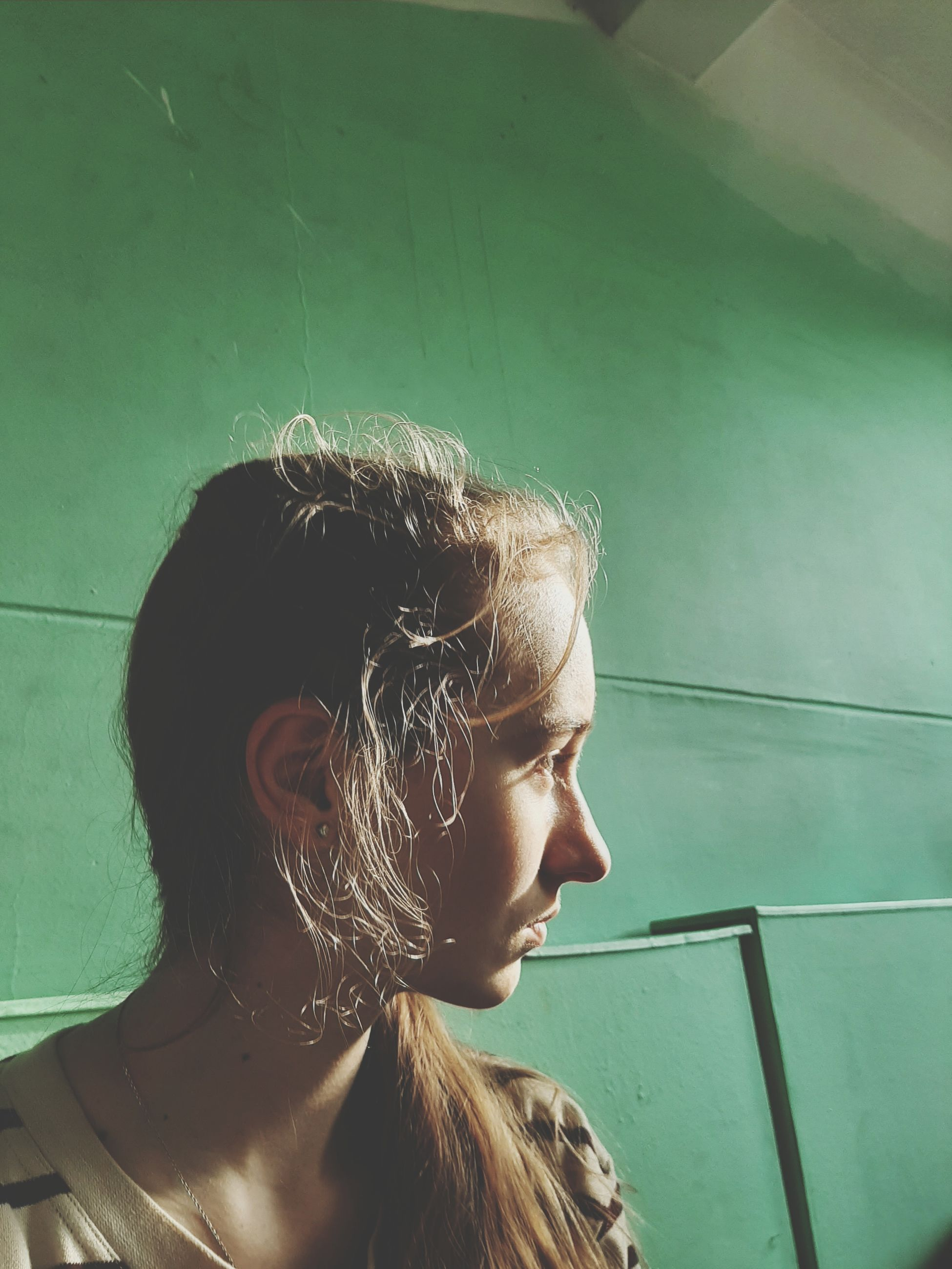 one person, headshot, real people, looking, hair, portrait, lifestyles, young adult, leisure activity, wall - building feature, looking away, young women, hairstyle, side view, long hair, indoors, day, women, contemplation, teenager, profile view