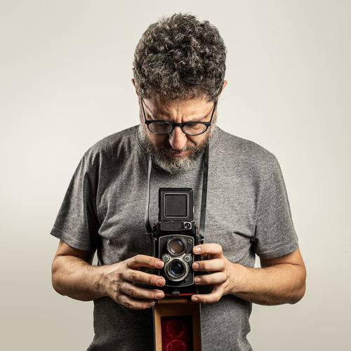 Man holding camera against white background