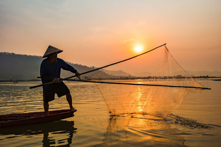 Fisherman on boat river sunset / Asia fisherman net using on wooden boat casting net sunset or sunrise in the Mekong river - Silhouette fisherman boat with mountain background life person countryside ASIA Asian  Background Beautiful Boat CAST Casting Catch Commercial Early Evening Finder Fish Fisherman Fishermen Fishing Food Forest Lake Landscape Laos Life Lifestyle Man Mekong Morning Myanmar Nature Net Ocean Outdoor People person River Sea Silhouette Sky Summer Sun Sunrise Sunset Thailand Throwing  Tourism Traditional Tropical Vietnam Vietnamese Water Working