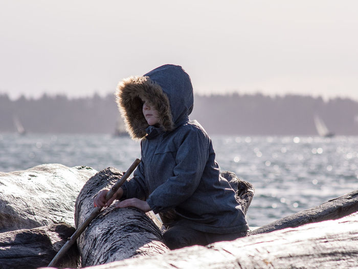 Side view of boy holding stick sitting on log by sea against sky