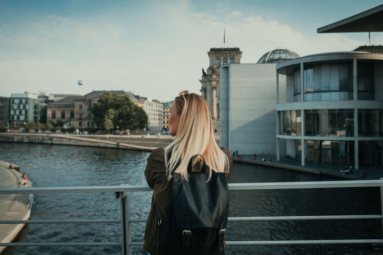 Woman standing on bridge over river in city against sky