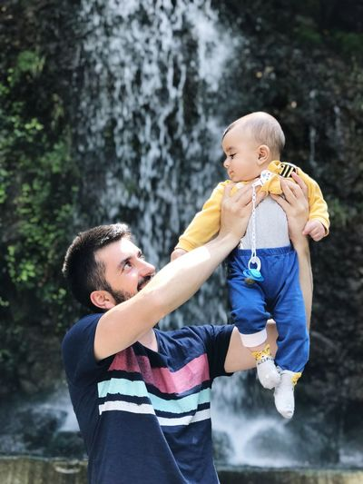 Father picking up son while standing against waterfall