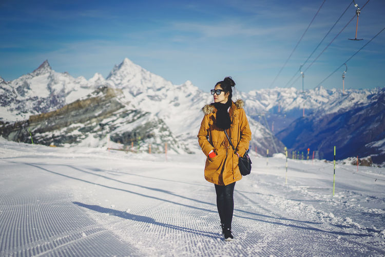 EyeEmNewHere Beauty In Nature Clothing Cold Temperature Front View Leisure Activity Lifestyles Looking At Camera Mountain Mountain Range Nature One Person Outdoors Real People Scenics - Nature Snow Snowcapped Mountain Standing Warm Clothing Winter Young Adult Young Women