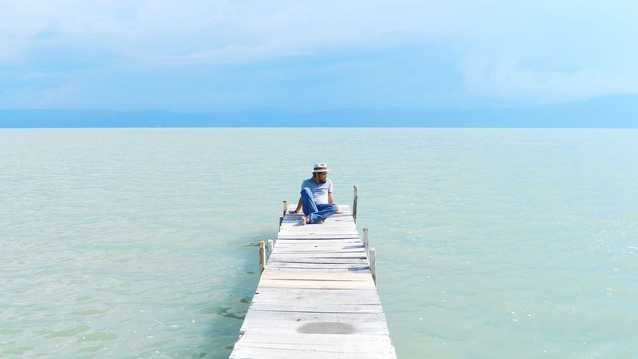 Mature Man Sitting On Pier Over Sea Against Sky During Sunny Day