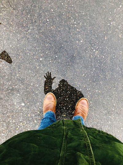 Low section of man standing on wet floor during rainy season