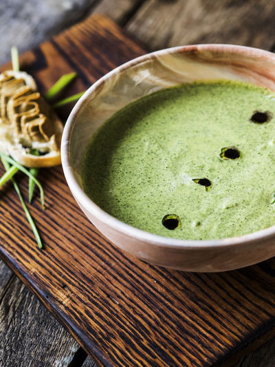 Close-Up Of Spinach Soup With Bread Served On Cutting Board