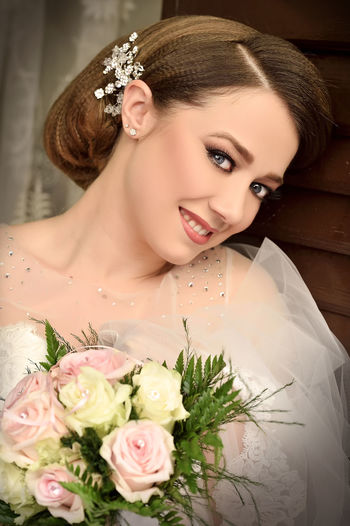 Close-up of beautiful bride holding bouquet while standing at home