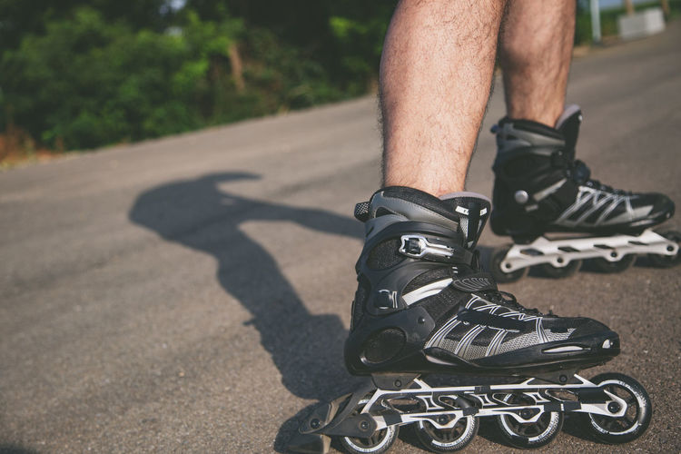Low section of man roller skating on road