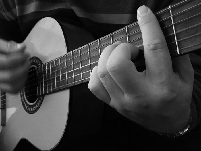 Midsection of musician playing acoustic guitar