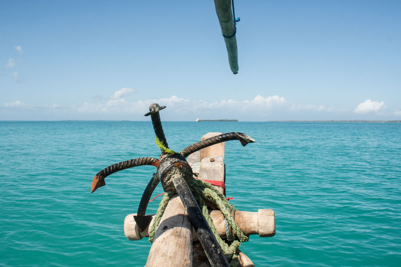 Anchor on boat in sea against blue sky during sunny day