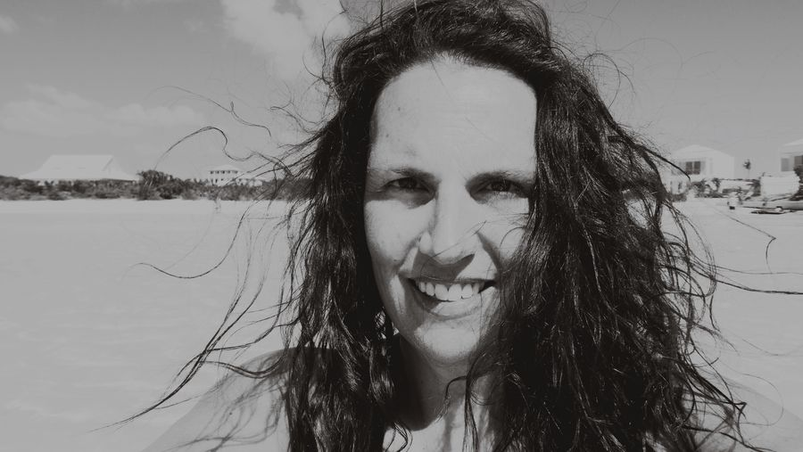 Portrait of smiling woman at beach against sky