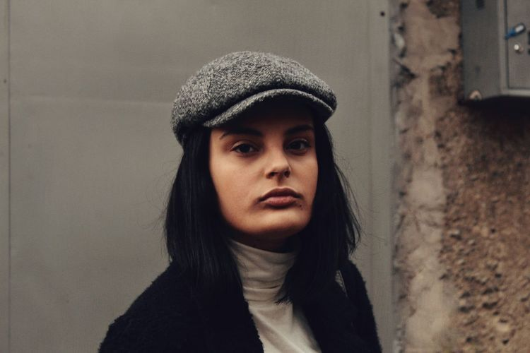 Portrait of confident young woman wearing flat cap against wall