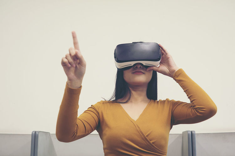 Woman wearing virtual reality simulator while pointing against clear sky