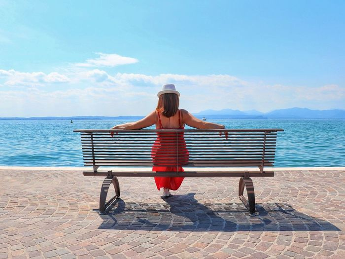 Rear view of woman sitting on bench at promenade against blue sky