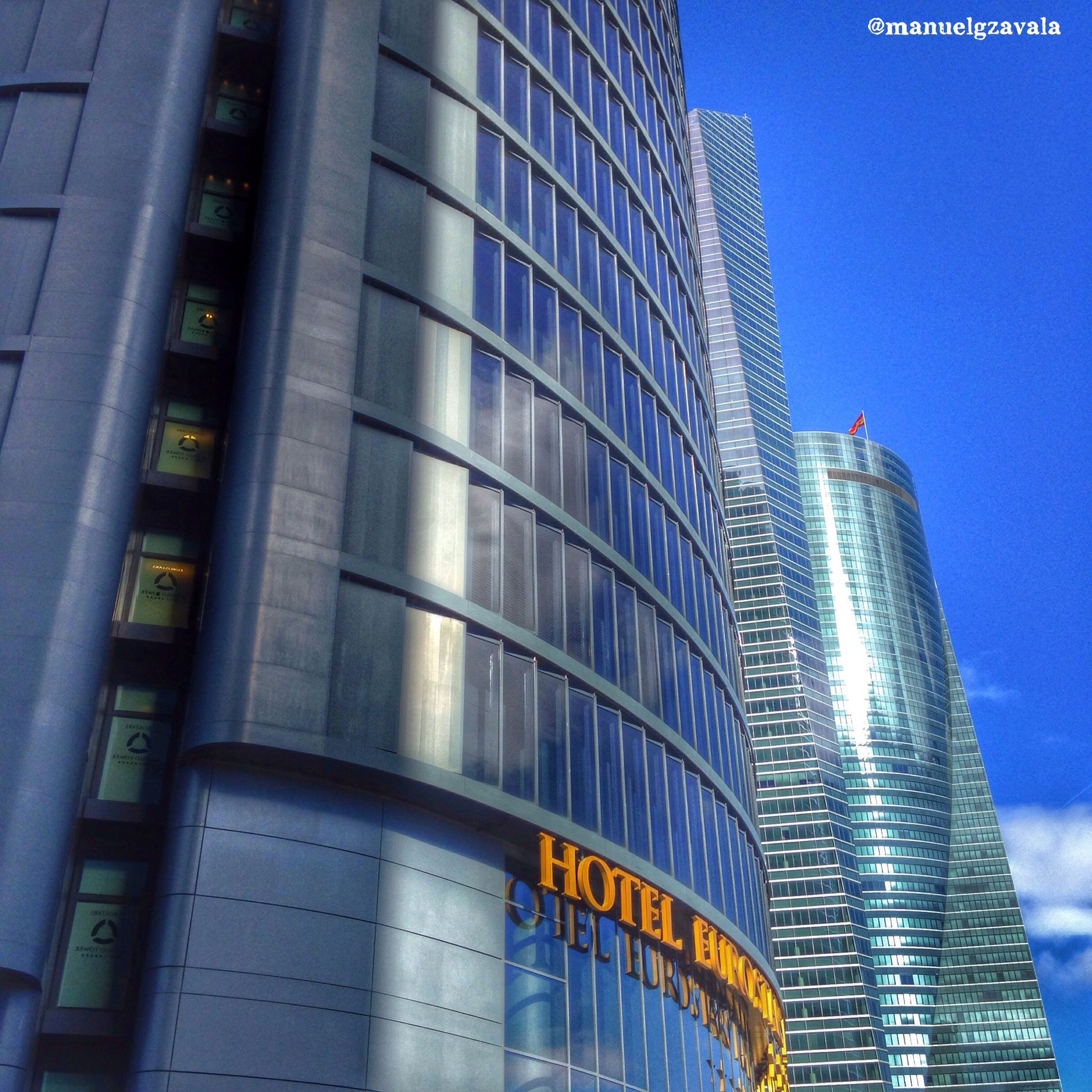 building exterior, architecture, built structure, low angle view, city, modern, office building, skyscraper, tall - high, building, tower, blue, glass - material, city life, reflection, window, sky, clear sky, outdoors, no people