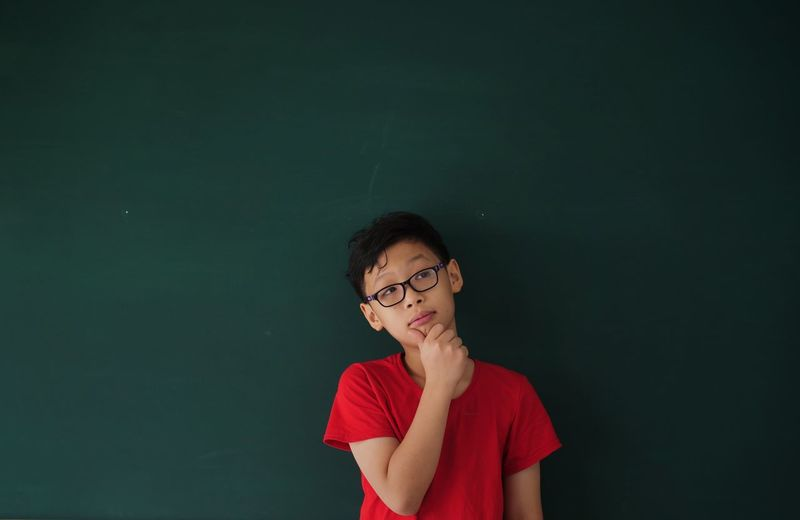 Thoughtful Boy Looking Away While Standing Against Blackboard In Classroom