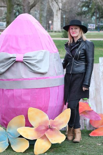 Portrait of smiling beautiful woman standing by large easter egg