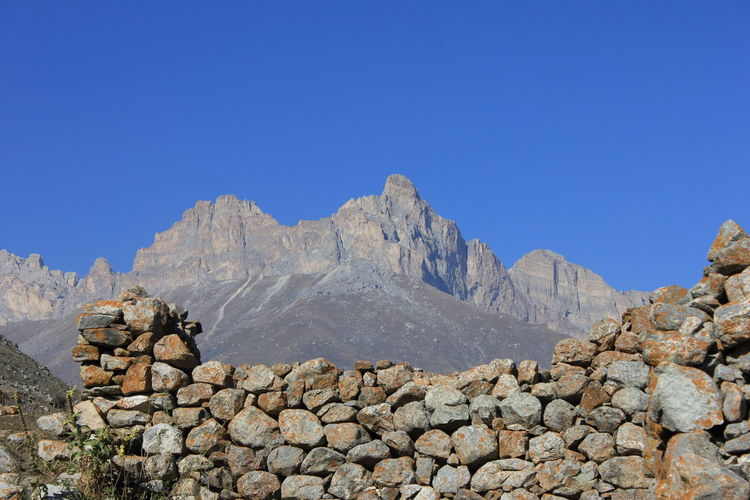 Stack of rocks on mountain against clear blue sky