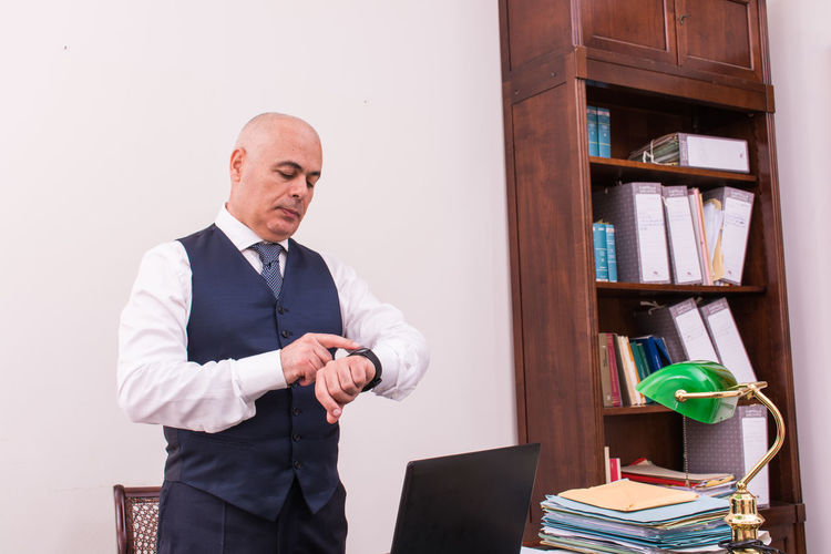 Businessman Looking At Wristwatch While Standing In Office