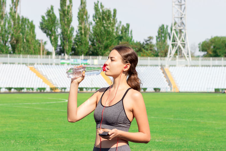 Young athlete drinking water while standing on sports track