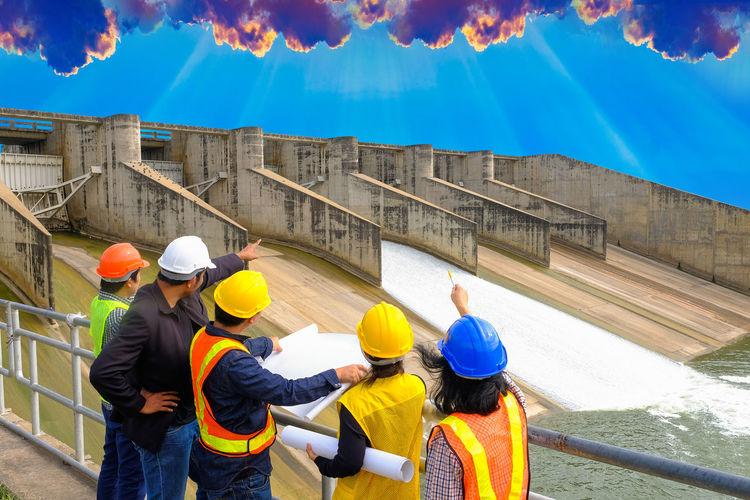 People working against orange sky