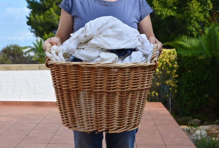 Laundry day. Woman carrying a wicker basket of wet laundry to be hung out to dry. Basket One Person Outdoors Day Front View Real People Standing Low Section Adults Only Freshness Adult Women Laundry Day Laundry Laundry Basket Holding Laundry Time Real Woman Real Life Household Chores