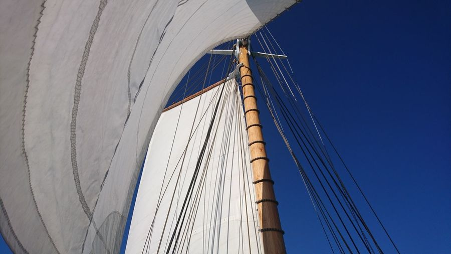 Low angle view of sails against clear blue sky