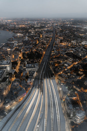 Aerial view of light trails on street amidst cityscape at sunset