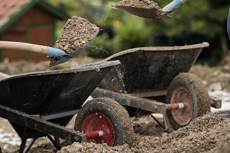 Dirt pouring in wheelbarrow at construction site