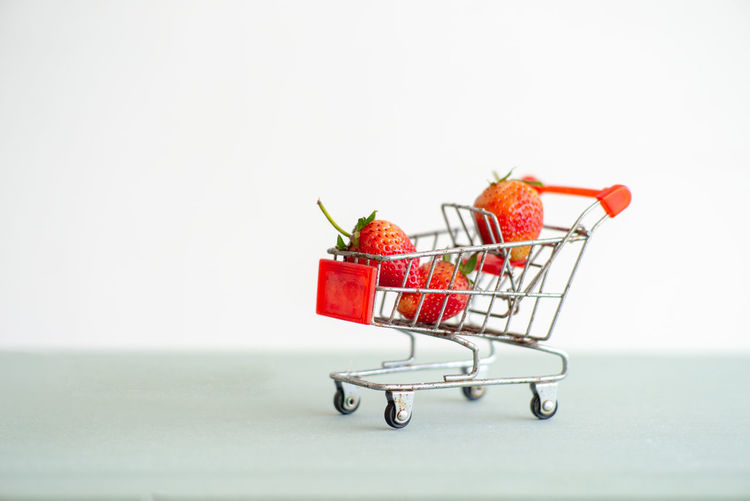 Closeup strawberries in the shopping trolley. Cart carrying the strawberry with the isolated background Supermarket Shopping Cart White Background Copy Space Healthy Eating Freshness Vitamin Food