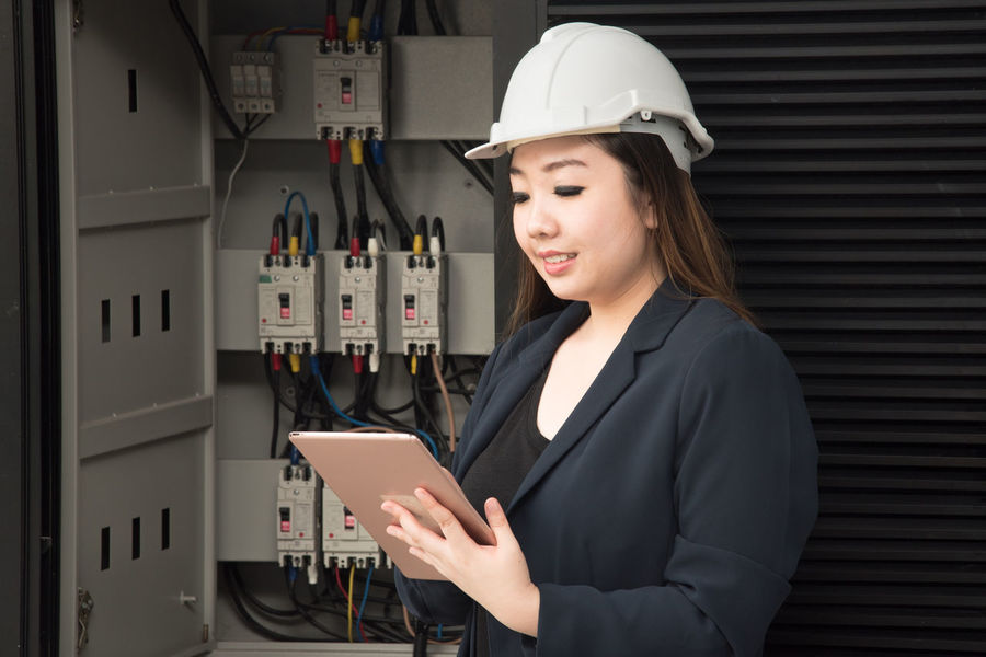 Adult Business Communication Connection Corporate Business Day Digital Tablet Hardhat  Headwear Helmet Holding Indoors  Occupation One Person One Young Woman Only People Real People Standing Technology Touch Screen Well-dressed Wireless Technology Working Young Adult Young Women