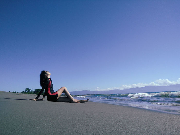 Young Woman Relaxing On Shore At Beach Against Blue Sky