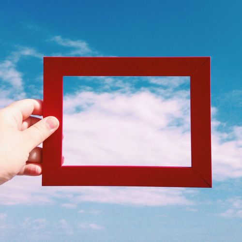 Hand holding red frame against sky