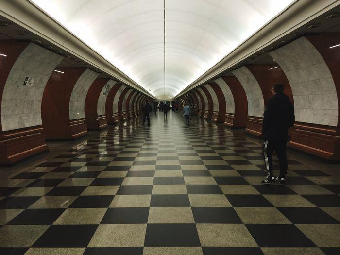 People Walking On Illuminated Metro Walkway